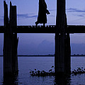 Buddhist monk walking over U Bein's bridge at dusk Print by Ruben Vicente