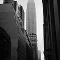 empire state building shrouded in mist in amongst dark cold buildings on 33rd Street new york city Print by Joe Fox