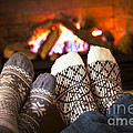 Feet warming by fireplace Poster by Elena Elisseeva
