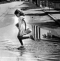 Girl Playing In A Puddle Print by Retro Images Archive