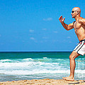 Healthy man running on the beach Poster by Anna Omelchenko