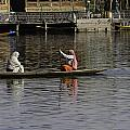 Ladies plying a small boat in the Dal Lake in Srinagar - in fron Print by Ashish Agarwal