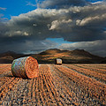 Landscape of hay bales in front of mountain range with dramatic  Poster by Matthew Gibson