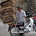 Man carrying cardboard on the back of his scooter Poster by Sami Sarkis