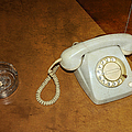 Old telephone and ashtray on brown table Poster by Matthias Hauser