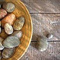 Spa rocks in wooden bowl on rustic wood Print by Sandra Cunningham