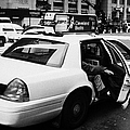 white caucasian passenger closes rear door of yellow cab on taxi rank at crosswalk on 7th Avenue Print by Joe Fox