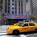 Yellow Cabs pass in front of Radio City Music Hall Poster by Amy Cicconi