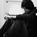 young dark haired teenage man sitting on the floor of the bathroom with back against the wall in the Poster by Joe Fox