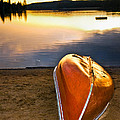 Lake sunset with canoe on beach Print by Elena Elisseeva