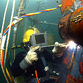 U.s. Navy Diver Welds A Repair Patch Poster by Stocktrek Images