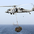 A Mh-60 Helicopter Transfers Cargo Print by Gert Kromhout