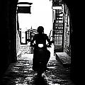 a scooter rider in the back light in a narrow street in Italy Print by Joana Kruse