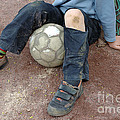 Boy with soccer ball sitting on dirty field Print by Matthias Hauser