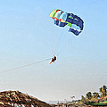 Couple parasailing over shacks Goa Poster by Kantilal Patel