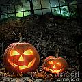 Halloween pumpkins on rocks  at night Poster by Sandra Cunningham