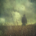 Hooded man walking in field with storm clouds Poster by Sandra Cunningham