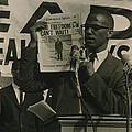 Malcolm X, Holding Up Newspaper Poster by Everett