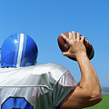 Rear View Of A Football Player Throwing A Football Poster by Stockbyte
