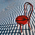 Red chair in sand Print by Garry Gay