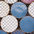 Rows of Stacked Barrels Behind a Fence Poster by Paul Edmondson