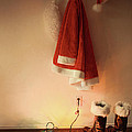Santa costume hanging on coat hook with christmas lights Print by Sandra Cunningham