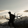 Silhouette Of Hunter Hiking With Elk Antlers Poster by Mike Kemp Images