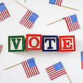 Studio Shot Of Small American Flags And Wooden Blocks With Text Vote Poster by Winslow Productions