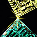 Two Circuit Boards Meeting At A Spot Of Light. Print by Tony Craddock