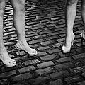 two young women wearing high heeled shoes and fake tan on cobblestones on a night out in dublin  Print by Joe Fox