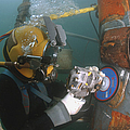 U.s. Navy Diver Uses A Grinder To File Poster by Stocktrek Images