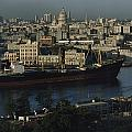 View Of City And A Massive Freighter Poster by James L. Stanfield