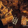 Woman burning candle at Troglodyte Sainte-Marie Madeleine Holy Cave Print by Sami Sarkis