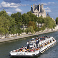 Sightseeing boat on river Seine to Louvre museum. Paris Print by BERNARD JAUBERT