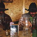 A Pair Of Cowboys Enjoy A Cup Of Coffee by Joel Sartore