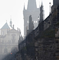 Charles bridge in the early morning fog by Michal Boubin