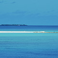 Fishing boat anchored on a white sand beach with a tropical island in the background in Maldives Poster by Sami Sarkis