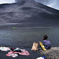 Girl washing clothes in a lake with the Mount Yasur volcano emitting smoke in the background Print by Sami Sarkis