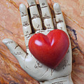 Plam reader hand holding red stone heart Print by Garry Gay