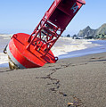 Red bell buoy on beach with bottle Print by Garry Gay