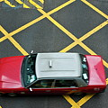 Red taxi cab driving over yellow lines in Hong Kong Poster by Sami Sarkis
